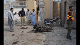 Pakistani security officials examine the site of a bombing on an entrance of a hospital in Dera Ismail Khan, Pakistan, Sunday, July 21, 2019. Police in Pakistan say gunmen opened fire on a police post and then bombed the entrance to a hospital as the wounded were being brought in.(AP Photo/Ishtiaq Mahsud)
