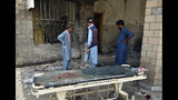 Hospital staff gather at the site of a bombing on an entrance of a hospital in Dera Ismail Khan, Pakistan, Sunday, July 21, 2019. Police in Pakistan say gunmen opened fire on a police post and then bombed the entrance to a hospital as the wounded were being brought in. (AP Photo/Ishtiaq Mahsud)