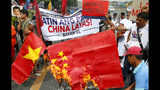 Protesters burn a mock Chinese flag as they prepare to march closer to the Philippine Congress to protest the 4th State of the Nation (SONA) address by President Rodrigo Duterte Monday, July 22, 2019 in suburban Quezon city, northeast of Manila, Philippines. Duterte is facing criticisms about his alleged closeness with China as well as the thousands of killings in his so-called war on drugs. (AP Photo/Bullit Marquez)