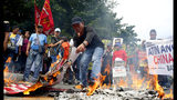 Protesters burn mock Chinese and U.S. flags as they prepare to march closer to the Philippine Congress to protest the 4th State of the Nation (SONA) address by President Rodrigo Duterte Monday, July 22, 2019 in suburban Quezon, city northeast of Manila, Philippines. Duterte is facing criticisms about his alleged closeness with China as well as the thousands of killings in his so-called war on drugs. (AP Photo/Bullit Marquez)
