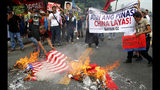 Protesters burn mock Chinese and U.S. flags as they prepare to march closer to the Philippine Congress to protest the 4th State of the Nation (SONA) address by President Rodrigo Duterte Monday, July 22, 2019 in suburban Quezon city, northeast of Manila, Philippines. Duterte is facing criticisms about his alleged closeness with China as well as the thousands of killings in his so-called war on drugs. (AP Photo/Bullit Marquez)