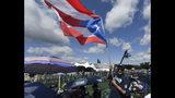 Miguel Rosario, de Atlantic City, Nueva Jersey, con una bandera de Puerto Rico a la espera del inicio de la ceremonia de exaltación al Salón de la Fama del béisbol, el domingo 21 de julio de 2019 en Cooperstown, Nueva York. (AP Foto/Hans Pennink)