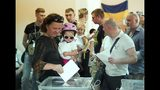 Ukrainians cast their ballots at a polling station during a parliamentary election in Kiev, Ukraine, Sunday, July 21, 2019. Ukrainians are voting in an early parliamentary election in which the new party of President Volodymyr Zelenskiy is set to take the largest share of votes. (AP Photo/Evgeniy Maloletka)