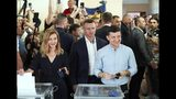 Ukrainian President Volodymyr Zelenskiy, right, and his wife Olena Zelenska cast their ballots at a polling station during a parliamentary election in Kiev, Ukraine, Sunday, July 21, 2019. Ukrainians are voting in an early parliamentary election in which the new party of President Volodymyr Zelenskiy is set to take the largest share of votes. (AP Photo/Evgeniy Maloletka)