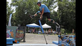 Fred Grzybowski, center, from Boston, does performs a dismount of his pogo stick during Pogopalooza, The World Championships of Pogo in Wilkinsburg, Pa., Saturday, July 20, 2019. (AP Photo/Gene J. Puskar)
