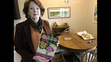 In this July 12, 2019 photo, former Iowa State University administrator Teresa McLaughlin poses at her Coralville, Iowa home with a magazine featuring Nature Connects, the outdoor sculptures made of Lego bricks that she managed. The university has withdrawn allegations of wrongdoing against McLaughlin and paid her $225,000 to settle a legal dispute that derailed the popular art program. (AP Photo/Ryan J. Foley)