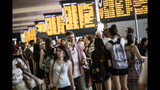 Passengers gather beneath display boards showing train times at Termini station in Rome, Monday, July 22, 2019. A suspected arson fire has forced cancellations of at least 42 high-speed trains in Italy on the heavily-traveled Milan-Naples corridor. (Massimo Percossi/ANSA via AP)