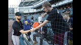 Geoffrey Boston, from Elgin, Ill., right, reaches for his hat through a seam in the newly extended protective netting along right field after Miami Marlins relief pitcher Nick Anderson, left, autographed a cap before a baseball game between the Marlins and the Chicago White Sox, Monday, July 22, 2019, in Chicago. (AP Photo/Charles Rex Arbogast)