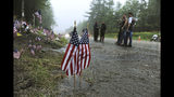 FILE - In this July 6, 2019, file photo, people view a memorial at the site where seven bikers riding with the Jarheads Motorcycle Club were killed in a collision last month in Randolph, N.H. State transportation officials in Massachusetts are expected to be questioned during a legislative oversight hearing on Monday, July 22, 2019, in Boston, about the Registry of Motor Vehicles' failure to suspend the commercial license of the truck driver charged in the crash that killed the seven motorcyclists in New Hampshire. (Paul Hayes/Caledonian-Record via AP, File)