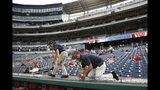 Workers adjust new netting that separates the infield from lower bowl seating before a postponed baseball game between the Colorado Rockies and the Washington Nationals, Monday, July 22, 2019, in Washington. (AP Photo/Patrick Semansky)
