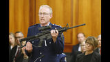 FILE - In this April 2, 2019, file photo, police acting superintendent Mike McIlraith shows New Zealand lawmakers an AR-15 style rifle similar to one of the weapons a gunman used to slaughter 51 people at two mosques, in Wellington, New Zealand. New Zealand's government is planning further restrictions on gun ownership in a proposed law that emphasizes owning guns is a privilege and not a right. (AP Photo/Nick Perry, File)