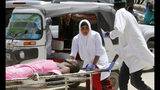 Medical workers help a man who was wounded in a car bomb attack, at Medina hospital, in Mogadishu, Somalia, Monday, July 22, 2019. A Somali police officer says a car bomb in the Somali capital has killed at least 10 people. Capt. Mohamed Hussein said at least 15 others were injured when the car bomb parked near a busy security checkpoint on the city's airport was detonated by remote control. (AP Photo/Farah Abdi Warsameh)