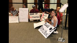 Students quietly protest outside the University of South Carolina Board of Trustees meeting room in Columbia, S.C., on Friday, July 19, 2019. Trustees are meeting to decide whether to hire retired Army general Robert Caslen as the university new president and the students say he is not qualified (AP Photo/Jeffrey Collins)