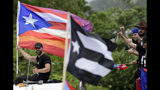 Puerto Rican singer Ricky Martin holds a Puerto Rico flag as he participates in a protest demanding the resignation of governor Ricardo Rossello, in San Juan, Puerto Rico, Friday, July 19, 2019. Protesters are demanding Rossello step down for his involvement in a private chat in which he used profanities to describe an ex-New York City councilwoman and a federal control board overseeing the island's finance. (AP Photo/Carlos Giusti)