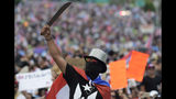 A demonstrator brandishes a machete during a march on Las Americas highway to demand the resignation of governor Ricardo Rossello, in San Juan, Puerto Rico, Monday, July 22, 2019. Protesters are demanding Rossello step down for his involvement in a private chat in which he used profanities to describe an ex-New York City councilwoman and a federal control board overseeing the island's finance. (AP Photo/Carlos Giusti)