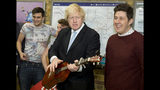 FILE - In this Monday, March 23, 2015 file photo Mayor of London Boris Johnson plays with a guitar in front of the busking band The Tailormade during a photocall to promote two new schemes aimed at supporting and promoting busking and street performance, at London Bridge Station in London. (AP Photo/Alastair Grant, File)