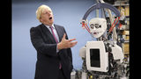 FILE - In this Thursday, July 20, 2017 file photo Britain's Foreign Secretary Boris Johnson gestures as he looks at a humanoid robot at Research Institute for Science and Engineering at Waseda University's campus in Tokyo. (AP Photo/Eugene Hoshiko, Pool, File)