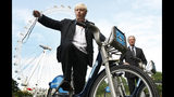 FILE - In this Friday, July 30, 2010 file photo, Boris Johnson, then Mayor of London, left, with the Chairman of Britain's Barclays Bank Marcus Agius as they poses for the media as a new cycle hire scheme starts in London. (AP Photo/Alastair Grant, File)