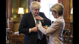 FILE - In this Thursday, Feb. 23, 2017 file photo British Foreign Secretary Boris Johnson has his tie straightened by his Australian counterpart Foreign Minister Julie Bishop in his office at the Foreign and Commonwealth Office in London. (Jack Taylor/Pool Photo via AP)