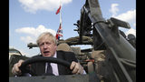 FILE - In this Thursday, June 21, 2018 file photo Britain's Foreign Secretary Boris Johnson talks to a British armed forces serviceman based in Orzysz, in northeastern Poland, during a ceremony at the Tomb of the Unknown Soldier and following talks on security with his Polish counterpart Jacek Czaputowicz in Warsaw, Poland. Boris Johnson aspires to be a modern-day Winston Churchill. Critics fear he's a British Donald Trump. Johnson won the contest to lead the governing Conservative Party on Tuesday July 23, 2019, and is set to be asked Wednesday by Queen Elizabeth II to become Britain's next prime minister. (AP Photo/Czarek Sokolowski, File)