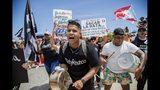 Manifestantes hacer sonar cacerolas durante una marcha por la autovía Las Américas para exigir la renuncia del gobernador, Ricardo Rosselló, en San Juan, Puerto Rico, el 22 de julio de 2019. (AP Foto/Dennis M. Rivera Pichardo)