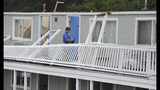 A Yarmouth building department worker surveys the damage to the second floor of the Cape Sands Inn where a tornado touched down ripping off the second floor of the structure, Tuesday, July 23, 2019, in West Yarmouth, Mass. The National Weather Service said radar showed that a tornado struck Yarmouth just after noon on Tuesday. (Steve Heaslip/The Cape Cod Times via AP)