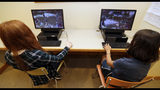 """Claire Hofstra, left, and Kaila Morris play """"Heroes of the Storm,"""" at Hathaway Brown School, Wednesday, July 10, 2019, in Shaker Heights, Ohio. Hathaway Brown launched the country's first varsity esports program at an all-girls school. Coach J Collins hopes to encourage more girls to stick with video games through their teenage years, something that might have a ripple effect across an industry grappling with gender disparity. (AP Photo/Tony Dejak)"""