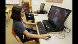 """Kaila Morris, foreground, plays """"Heroes of the Storm,"""" at Hathaway Brown School, Wednesday, July 10, 2019, in Shaker Heights, Ohio. Hathaway Brown launched the country's first varsity esports program at an all-girls school. (AP Photo/Tony Dejak)"""