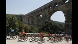 The pack rides next to the Pont du Gard during the sixteenth stage of the Tour de France cycling race over 117 kilometers (73 miles) with start and finish in Nimes, France, Tuesday, July 23, 2019. (AP Photo/ Christophe Ena)