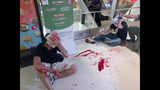 In this Sunday, July 21, 2019, photo, two men in black shirts cover their heads as they bleed after being attacked by thugs in white shirts at a subway station in New Territory in Hong Kong. China doesn't want to intervene in Hong Kong's protests but that doesn't mean it won't, as the movement enters its seventh week. (Apple Daily via AP)