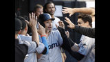Miami Marlins' Neil Walker celebrates in the dugout after scoring on a double by Starlin Castro during the fourth inning of a baseball game Tuesday, July 23, 2019, in Chicago. (AP Photo/Charles Rex Arbogast)