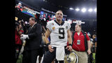 FILE - In This Oct. 8, 2018, file photo, New Orleans Saints quarterback Drew Brees (9) reacts after breaking the NFL record for all-time passing yards during, the first half of an NFL football game against the Washington Redskins in New Orleans. Visitors to the Pro Football Hall of Fame can see both the football Drew Brees threw in becoming the NFL's all-time passing yards leader and the uniform the Saints quarterback wore while making history. Mark Baker, the hall's president and chief executive officer, holds the ball at left. (AP Photo/Gerald Herbert, File)