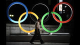 A man walks past the Olympic rings Tuesday, July 23, 2019, in Tokyo, as Japan marks a year-to-go until hosting the summer games with Olympic medals being unveiled Wednesday as part of daylong ceremonies around the Japanese capital. The Summer Olympics will return to Tokyo next year for the first time since 1964. (AP Photo/Jae C. Hong)