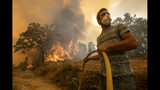 A villager tries to extinguish a wildfire at the village of Chaveira, near Macao, in central Portugal on Monday, July 22, 2019. More than 1,000 firefighters are battling a major wildfire amid scorching temperatures in Portugal, where forest blazes wreak destruction every summer. About 90% of the fire area in the Castelo Branco district, 200 kilometers (about 125 miles) northeast of the capital Lisbon, has been brought under control during cooler overnight temperatures, according to a local Civil Protection Agency commander. (AP Photo/Sergio Azenha)