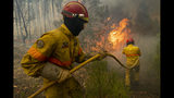 Firefighters try to extinguish a wildfire at the village of Chaveira, near Macao, in central Portugal on Monday, July 22, 2019. More than 1,000 firefighters are battling a major wildfire amid scorching temperatures in Portugal, where forest blazes wreak destruction every summer. About 90% of the fire area in the Castelo Branco district, 200 kilometers (about 125 miles) northeast of the capital Lisbon, has been brought under control during cooler overnight temperatures, according to a local Civil Protection Agency commander. (AP Photo/Sergio Azenha)