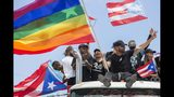 Ricky Martin, flying a gay pride flag, joins a protest to demand the resignation of Governor Ricardo Rossello from office, in San Juan, Puerto Rico, Monday, July 22, 2019. Protesters are demanding Rossello step down for his involvement in a private chat in which he used profanities to describe an ex-New York City councilwoman and a federal control board overseeing the island's finance. (AP Photo/Dennis M. Rivera Pichardo)