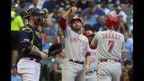 El jugador de los Rojos de Cincinnati Eugenio Suárez es felicitado por Joey Votto tras pegar un jonrón de dos carreras en el primer inning de su juego de béisbol contra los Cerveceros de Milwaukee, el martes 23 de julio de 2019, en Milwaukee. (AP Foto/Morry Gash)