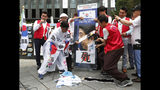 "A South Korean protester uses scissors to cut an image of Japanese Prime Minister Shinzo Abe during a rally denouncing the Japanese government's decision on their exports to South Korea in front of the Japanese Embassy in Seoul, South Korea, Tuesday, July 23, 2019. The signs read ""Punish economic aggression."" (AP Photo/Ahn Young-joon)"