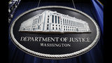 FILE - In this Thursday, April 18, 2019, file photo, a sign for the Department of Justice hangs in the press briefing room at the Justice Department, in Washington. The U.S. Department of Justice is opening a sweeping antitrust investigation of major technology companies and whether their online platforms have hurt competition, suppressed innovation or otherwise harmed consumers. (AP Photo/Patrick Semansky, File)