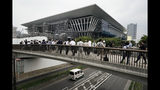 FILE - In this July 3, 2019, file photo, members of the media gather outside the Tokyo Aquatics Center, a venue for swimming and diving at the Tokyo 2020 Summer Olympics in Tokyo. The Olympics will be simply a sideshow for some Tokyo visitors, astounded by the cleanliness, courtesy and order. Japan's sprawling capital is a dense mix of the traditional and eccentric where bowing meets bustle. (AP Photo/Jae C. Hong, File)