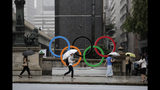 Commuters walk past the Olympic Rings Tuesday, July 23, 2019, in Tokyo. To mark the year-to-go mark, the gold, silver and bronze Olympic medals are to be unveiled Wednesday as part of daylong ceremonies around the Japanese capital. Tokyo's 1964 Olympics showcased bullet trains, futuristic designs and a new expressway, underlining Japan's recovery following World War II. Those games were the first seen worldwide by early satellites, sending the Olympics into a new era. (AP Photo/Jae C. Hong)