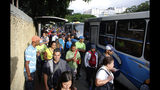 People stand in a bus line in Caracas, Venezuela, Tuesday, July 23, 2019. The lights were returning to life early Tuesday across Venezuela following a massive blackout a day earlier that crippled communications, froze the Caracas metro and snarled rush hour traffic, officials said. (AP Photo/Leonardo Fernandez)