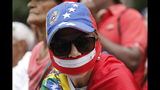 A woman wearing a cap with a Venezuelan national flag motif and a zipper over her mouth, waits for the arrival of opposition leader and self-proclaimed interim president of Venezuela Juan Guaido, in Caracas, Venezuela, Tuesday, July 23, 2019. The lights were returning to life early Tuesday across Venezuela following a massive blackout a day earlier that crippled communications, froze the Caracas metro and snarled rush hour traffic, officials said. (AP Photo/Ariana Cubillos)