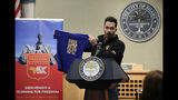 """Claudio Moreau, of Venezuela, holds up a T-shirt reading """"Freedom for All"""" during a news conference regarding local efforts to support the Venezuelan democracy movement, at Miami City Hall, Monday, July 22, 2019, in Miami. The City of Miami will host a 5K run July 28 to raise money for the movement. (AP Photo/Lynne Sladky)"""