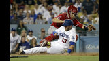 Los Angeles Dodgers' Max Muncy, bottom, scores past Los Angeles Angels catcher Dustin Garneau on an infield single by Russell Martin during the sixth inning of a baseball game, Tuesday, July 23, 2019, in Los Angeles. (AP Photo/Marcio Jose Sanchez)