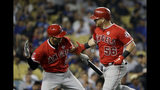 Los Angeles Angels' Kole Calhoun, right, celebrates his solo home run with teammate Andrelton Simmons during the seventh inning of a baseball game against the Los Angeles Dodgers, Tuesday, July 23, 2019, in Los Angeles. (AP Photo/Marcio Jose Sanchez)
