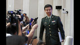 """China's Defense Ministry spokesman Wu Qian leaves as journalists are asking question on Hong Kong's recent protests after a press conference at the State Council Information Office in Beijing, Wednesday, July 24, 2019. China says it will not """"renounce the use of force"""" in efforts to reunify Taiwan with the mainland and vows to take all necessary military measures to defeat """"separatists."""" (AP Photo/Andy Wong)"""