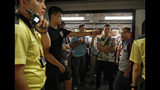 A protester in black shirt gestures against some passengers as he blocked the train doors stopping the trains leaving at a subway platform in Hong Kong Wednesday, July 24, 2019. Subway train service was disrupted during morning rush hour after dozens of protesters staged what they called a disobedience movement to protest over a Sunday mob attack at a subway station. (AP Photo/Vincent Yu)
