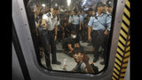 Two protesters are surrounded by police officers while sitting on the floor saying he is injured at a subway platform in Hong Kong Wednesday, July 24, 2019. Subway train service was disrupted during morning rush hour after dozens of protesters staged what they called a disobedience movement to protest over a Sunday mob attack at a subway station. (AP Photo/Vincent Yu)