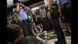A protester, center, is surrounded by police officers while sitting on the floor saying he is injured at a subway platform in Hong Kong Wednesday, July 24, 2019. Subway train service was disrupted during morning rush hour after dozens of protesters staged what they called a disobedience movement to protest over a Sunday mob attack at a subway station. (AP Photo/Vincent Yu)